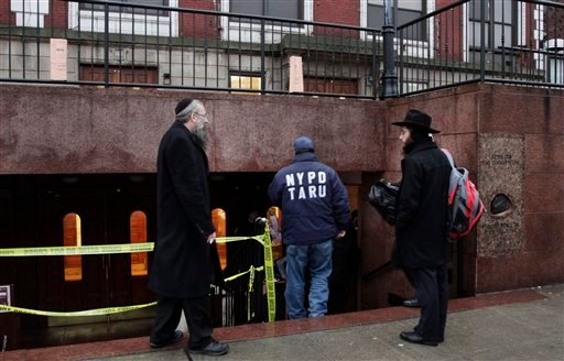 Members of the Lubavitch community watch a police officer enter Chabad-Lubavitch Hasidic headquarters, Tuesday, Dec. 9, 2014, in New York. (AP Photo/Mark Lennihan)