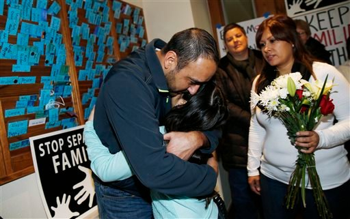 Arturo Hernandez hugs his daughter, Andrea, as his wife, Ana Sauzameda, right, and Rev. Anne Dunlap of the United Church of Christ look on during news conference in church in Denver Dec. 9, 2014. (AP Photo/David Zalubowski)