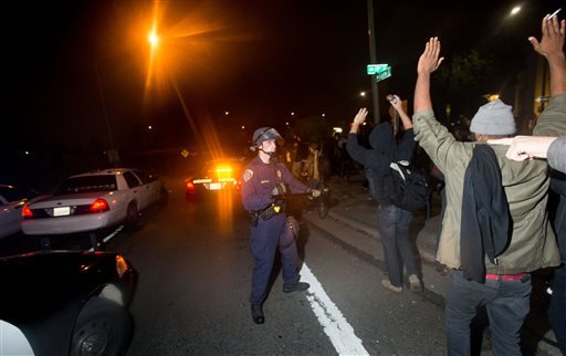 California Highway Patrol Officer Kopriva keeps protesters marching against police violence from storming Interstate 980 on Tuesday, Dec. 9, 2014, in Oakland, Calif. (AP Photo/Noah Berger)