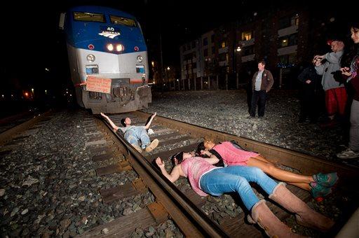 Protesters block an Amtrak train in Berkeley, Calif., on Monday, Dec. 8, 2014. (AP Photo/Noah Berger)