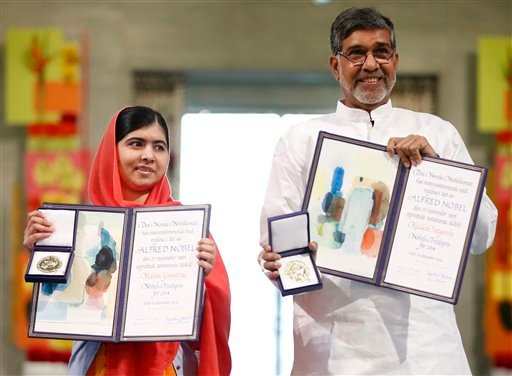 Nobel Peace Prize winners Malala Yousafzai from Pakistan and Kailash Satyarthi of India hold their Nobel Peace Prize diplomas and medals during the Nobel Peace Prize award ceremony in Oslo, Norway Dec. 10, 2014. (AP Photo/Cornelius Poppe, NTB Scanpix)