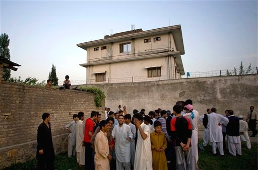 In this May 3, 2011 file photo, local residents gather outside a house, where al-Qaida leader Osama bin Laden was caught and killed in Abbottabad, Pakistan. (AP Photo/B.K.Bangash,File)