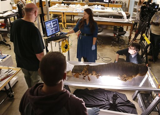 JP Brown, Regenstein Conservator at the Field Museum, right, and his team from left, Michael Marozas, Brian Cory, and Morgan Nau, photograph the backside of the mummified body of Minirdis, a 14-year-old Egyptian boy. (AP)