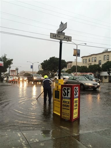 This photo provided by Yvonne Pham shows city employee working to clear the drains of a flooded San Francsico street on Thursday, Dec. 11, 2014.