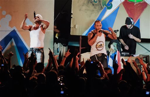 In this April 23, 2010 photo, members of Los Aldeanos, Aldo Rodriguez, left, and Bian Rodriguez, center, perform in concert at the Acapulco Theater in Havana, Cuba.