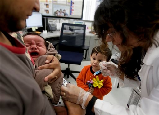 Julietta Losoyo, right, a Registered Nurse at the San Diego Public Health Center gives Derek Lucero a whooping cough injection while in his fathers Leonel's arms as his brother Iker, 2, looks on, Wednesday, Dec. 10, 2014 in San Diego.