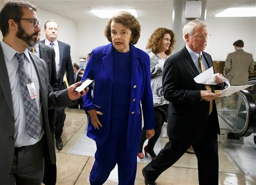 Senate Intelligence Committee Chair Sen. Dianne Feinstein, D-Calif., center, and Sen. Roger Wicker, R-Miss., right, rush to the Senate floor on Capitol Hill in Washington, Thursday, Dec. 11, 2014, for a procedural vote to advance the $585 billion defense
