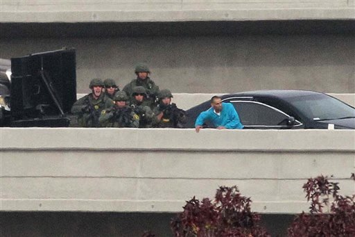 Police approach Daniel Diego Perez as he tries to jump off a freeway bridge in Santee, Calif. on Thursday, Dec. 11, 2014.