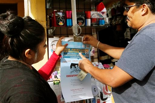 This Dec. 10, 2014 photo shows Lucero Vega watches as Tony Bernabe, right, posts a flier in downtown Los Angeles advertising a massive information session scheduled for this weekend. (AP)