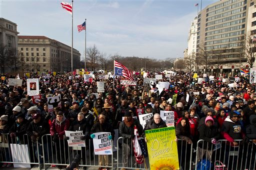 Demonstrators chant at Freedom Plaza in Washington, Saturday, Dec. 13, 2014, during the Justice for All rally and march. More than 10,000 protesters are converging on Washington in an effort to bring attention to the deaths of unarmed black men at the han