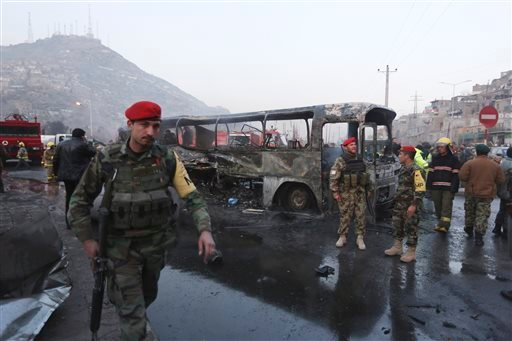 Afghan soldiers stand around a damaged bus at the site of a suicide attack by the Taliban in Kabul, Afghanistan, Saturday, Dec. 13, 2014. A senior Afghan defense official said that the suicide bomber struck the Defense Ministry bus carrying Afghan Army pe