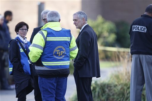 Portland Mayor Charlie Hales arrives near Rosemary Anderson High School, where a shooting took place Friday, Dec. 12, 2014. A shooter wounded two boys and a girl outside the high school Friday in what may be a gang-related attack, police said. (AP Photo/T