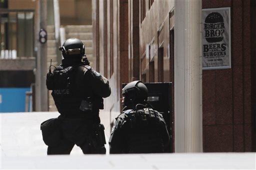 Police stand at the ready close to a cafe under siege in Martin Place in the central business district of Sydney, Australia, Monday, Dec. 15, 2014. New South Wales state police would not say what was happening inside the cafe or whether hostages were bein
