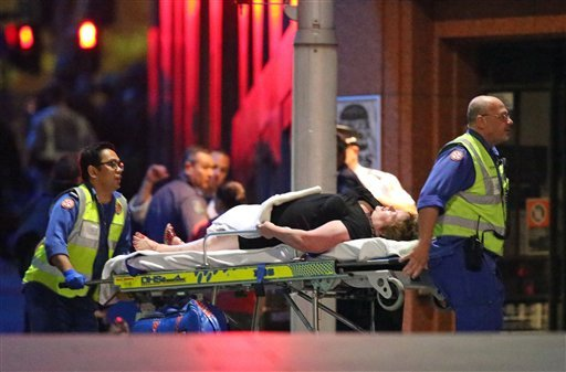An injured hostage is wheeled to an ambulance after shots were fired during a cafe siege at Martin Place in the central business district of Sydney, Australia, Tuesday, Dec. 16, 2014.