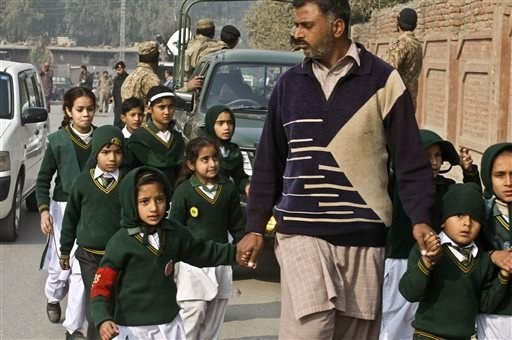 A plainclothes security officer escorts students evacuated from a school as Taliban fighters attack another school nearby in Peshawar, Pakistan, Tuesday, Dec. 16, 2014. Taliban gunmen stormed a military-run school in the northwestern Pakistani city, killi
