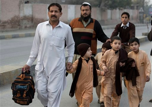 Pakistani parents escort their children outside a school attacked by the Taliban in Peshawar, Pakistan, Tuesday, Tuesday, Dec. 16, 2014. Taliban gunmen stormed a military-run school in the northwestern Pakistani city of Peshawar on Tuesday, killing and wo