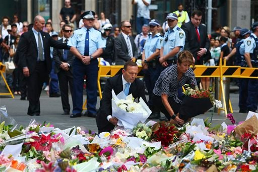 Australian Prime Minister Tony Abbott and his wife Margie pay their respect to the victims of the siege in Martin Place in Sydney central business district, Australia. Tuesday, Dec. 16, 2014. Abbott has laid flowers at a makeshift memorial in Sydney for t