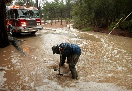 Property manager Alan Lambert works to clear a drain to minimize flooding at a client's home Monday, Dec. 15, 2014, in Pebble Beach, Calif. (AP)