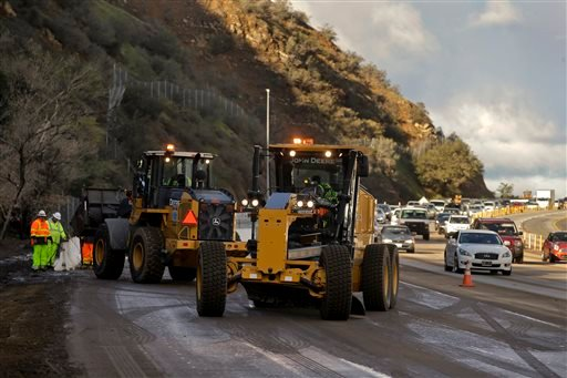 Caltrans crews work to clean up a torrent of mud and rocks covering part of State Route 91 in Orange County early Wednesday, Dec. 17, 2014, in Yorba Linda, Calif. (AP Photo/Chris Carlson)