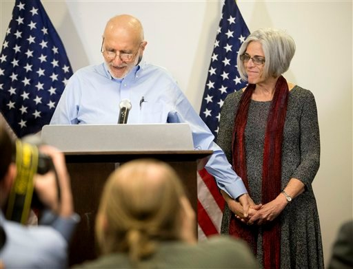 Alan Gross holds his wife Judy's hand while during a news conference at his lawyer's office in Washington, Wednesday, Dec. 17, 2014. Gross was released from Cuba after 5 years in a Cuban prison. (AP Photo/Pablo Martinez Monsivais)