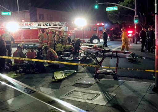 In this Wednesday, Dec. 17, 2014 photo provided by Mike Lewis, firefighters attend to a victim after a driver suspected of being intoxicated hit a group of pedestrians outside a church as a Christmas service ended in Redondo Beach, Calif. (AP)