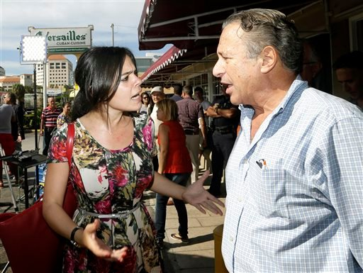 Cuban-American and pro-Obama supporter Claudia Hernandez, left, argues with anti-Castro protester Daniel Tarrab, right, in the Little Havana area of Miami, Thursday, Dec. 18, 2014. (AP)