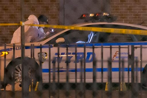 Investigators work at the scene where two NYPD officers were shot, Saturday, Dec. 20, 2014 in the Bedford-Stuyvesant neighborhood of the Brooklyn borough of New York. Police said an armed man walked up to two officers sitting inside the patrol car and ope