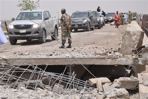 In this Sunday, May 11, 2014 file photo, A soldier and government officials inspects the bridge that link Nigeria and Cameroon following an attacked by Islamic militants in Gambaru, Nigeria. Thousands of members of Nigeria's home-grown Islamic extremist B