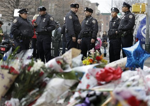 New York City police officers gather near a makeshift memorial near the site where fellow officers Rafael Ramos and Wenjian Liu were murdered in the Brooklyn borough of New York, Monday, Dec. 22, 2014. Police say Ismaaiyl Brinsley ambushed the two officer