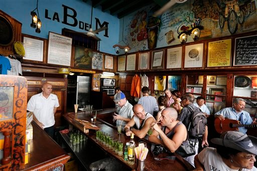 In this Dec. 19, 2014 photo, tourists fill the famous La Bodeguita del Medio bar where U.S. author Ernest Hemingway used to drink in Old Havana, Cuba. Experts don't expect American tourists to flood Cuba soon after new travel regulations are established,