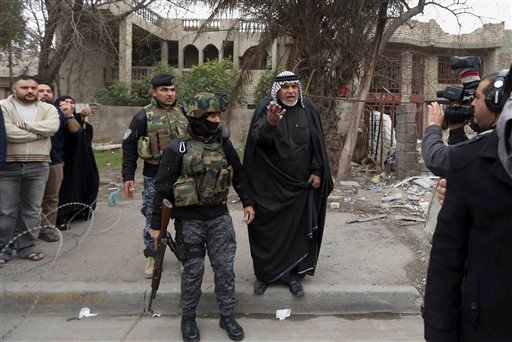 "In this photo taken Tuesday, Dec. 16, 2014, a man, center, expresses his anger at Haider Ali Motar, not seen, as they perform a scene from ""In the Grip of the Law,"" a reality show produced by Iraqi state TV, in Baghdad, Iraq."