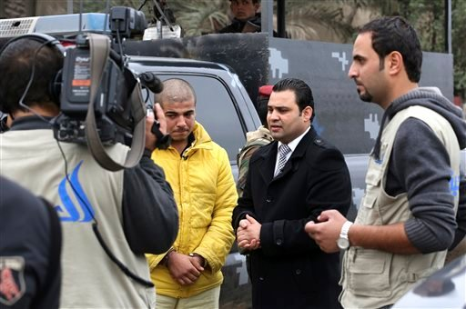 "In this Tuesday, Dec 16, 2014 photo, Ahmed Hassan, a reality show host, center right, stands next to Haider Ali Motar, as the TV crew films ""In the Grip of the Law,"" a reality show produced by Iraqi state TV, in Baghdad, Iraq."
