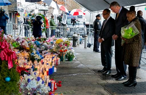 From left, Pastor Michael Durso, New York City Mayor Bill de Blasio and New York City first lady Chirlane McCray visit a makeshift memorial Tuesday, Dec. 23, 2014, near the site where two New York Police Department officers were killed. (AP)