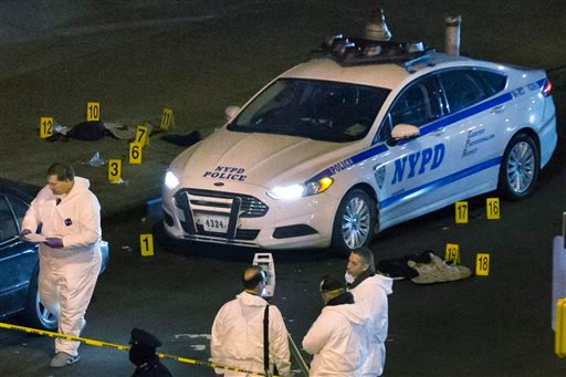 FILE - In this Saturday, Dec. 20, 2014, file photo, bulletproof vests lie on each side of a New York Police Department patrol car as investigators work at the scene where two NYPD officers were shot. (AP)