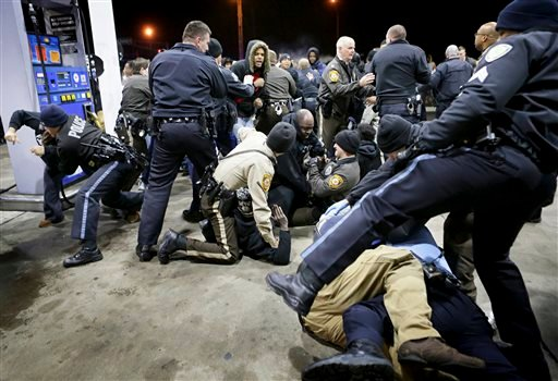 Police try to control a crowd Wednesday, Dec. 24, 2014, on the lot of a gas station following a shooting Tuesday in Berkeley, Mo.
