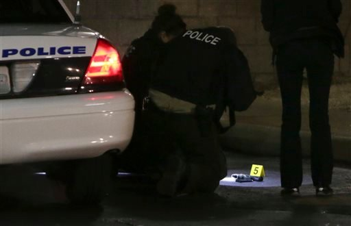 Police photograph a gun on the ground Wednesday, Dec. 24, 2014, following a shooting Tuesday at a gas station in Berkeley, Mo.