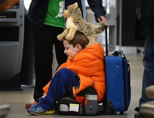David Welborn, 7, sits in the lost luggage line at the Delta Airlines desk at RDU International Airport on Tuesday, Dec. 23, 2014. (AP)