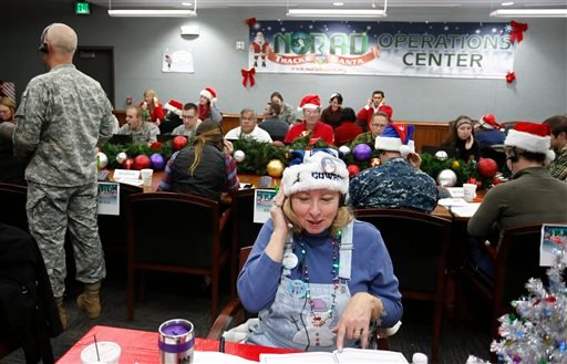 Volunteer Patty Shook takes a phone call from a child asking where Santa is and when he will deliver presents to her home, inside a phone-in center during the annual NORAD Tracks Santa Operation.