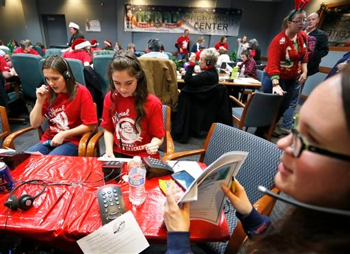 NORAD Santa Tracker volunteers, right to left, Michele Bergeman, 31, Geni Brant, 15, and Lauren Stolk, 14, take phone calls from children asking where Santa is and when he will deliver presents to their homes.