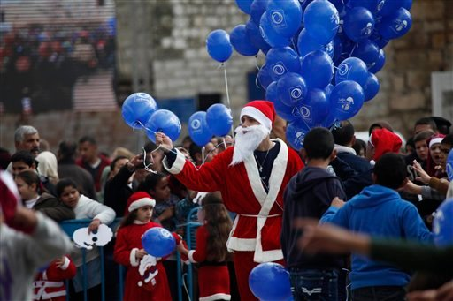 A Palestinian dressed as Santa Claus holds balloons at Manger Square, outside the Church of the Nativity, traditionally believed by Christians to be the birthplace of Jesus Christ, in the West Bank city of Bethlehem on Christmas Eve. (AP)