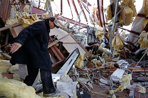 Sandra McDaniel walks through the remains of the product showroom for Jack Morris Gas Company in Columbia, Miss., Wednesday, Dec. 24, 2014. (AP)