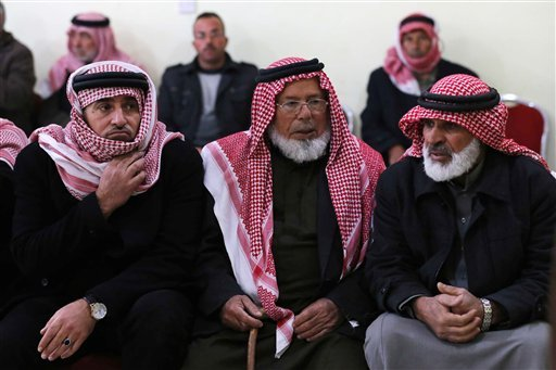 Friends and relatives of Mu'ath Safi al-Kaseasbeh, a Jordanian pilot captured by the Islamic State group, gather in the town of Aey near Al Karak in southern Jordan, Wednesday, Dec. 24, 2014. Islamic State militants captured the Jordanian pilot after his