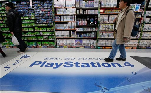 In this Thursday, Dec. 25, 2014 photo, a shopper walks on the logo of Sony's PlayStation 4 at an electronics store in Tokyo. Sony's online PlayStation store and Microsoft's Xbox site suffered disruptions to users on Christmas Day in the latest possible cy