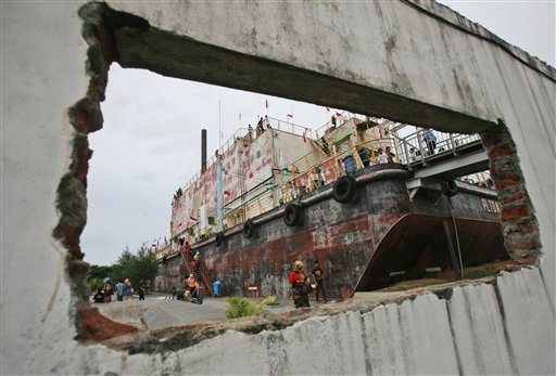People are seen through a hole in the wall of a damaged building, as they visit a giant steel barge that housed a diesel power generator swept ashore by the Indian Ocean tsunami ten years ago, in Banda Aceh, Aceh province, Indonesia, Friday, Dec. 26, 2014