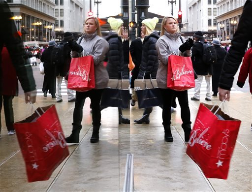 In this Dec. 24, 2014 file photo, last minute Christmas shoppers are reflected in a store's window as they walk through Chicago's Loop. After enduring a brutal winter, businesses, consumers and investors showed renewed vigor as 2014 wore on and set themse
