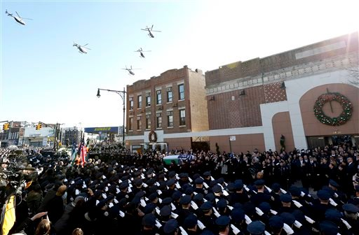 Law enforcement helicopters fly over Christ Tabernacle Church, where the casket of New York City police officer Rafael Ramos is carried by pallbearers, center, in the Glendale section of Queens, Saturday, Dec. 27, 2014, in New York. Ramos and his partner,