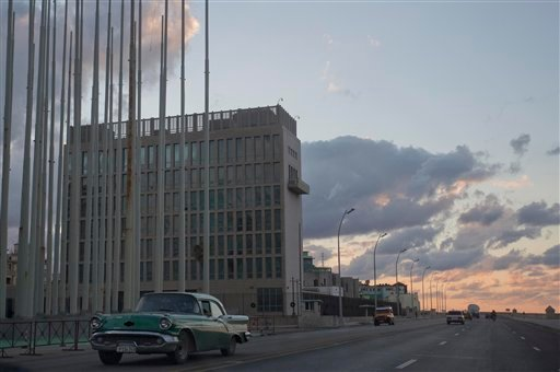 This Dec. 17, 2014 file photo shows a classic American car driving past the U.S. Interests Section buidling in Havana, Cuba. A half-century after Washington severed relations with Cuba, the seven-story mission is set to become a full-fledged embassy. The