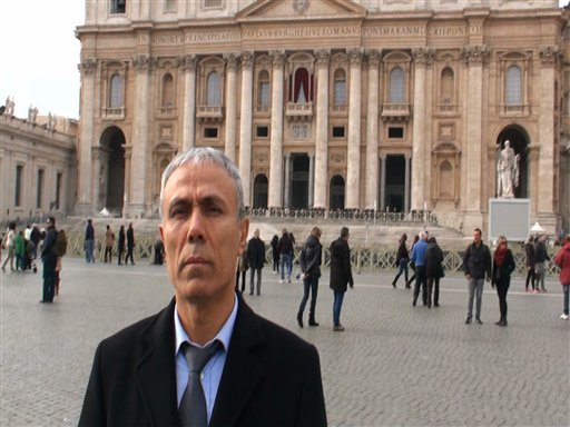 In this image taken from a video provided by Adnkronos International, Ali Agca stands in front of St. Peter's Basilica at the Vatican, Saturday, Dec. 27, 2014. The Turkish gunman who shot and wounded John Paul II in 1981 laid white flowers Saturday on the