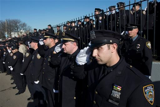 Police officers salute as the hearse of New York city police officer Rafael Ramos drives along his funeral procession route in the Glendale section of Queens, Saturday, Dec. 27, 2014, in New York. Ramos and his partner, officer Wenjian Liu, were killed De