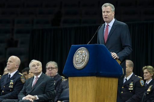 New York City Mayor Bill de Blasio speaks alongside NYPD police commissioner Bill Bratton, second from left, and chief of department James O'Neill, left, during a New York Police Academy graduation ceremony, Monday Dec. 29, 2014. (AP)